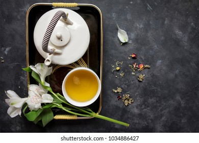 A Japanese teapot on a black tray with a cup of green tea and white lilies.  The bacground is a dark gray, textured surface with a scattering of loose tea.