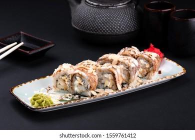 Japanese tempura fried sushi roll with tempura, cream cheese, eel, teriyaki soy sauce and chopsticks on black background. Sushi menu. Asian food and green tea teapot, copy space. Sashimi set