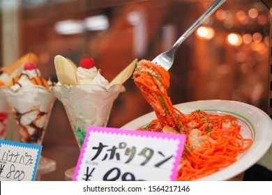"""Japanese text is """"Napolitan pasta"""", """"Banana sweet"""". Sample food in show window at restaurant."""