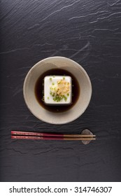 Japanese tofu, Japanese soft cold tofu with sauce in a dish on dining table with chopstick
