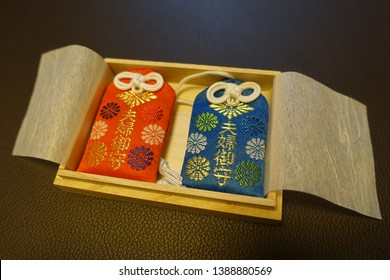 "Japanese Traditional Couple Pair Charms (Amulets) in the Wooden Box. The Japanese Characters means ""Couple Pair Charms (Amulets)"". No Logo or Trademark."