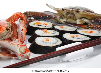 Japanese traditional Cuisine - Roll with Cucumber , Cream Cheese with raw Tuna and Salmon inside. on black dish with red and blue crabs . shallow dof