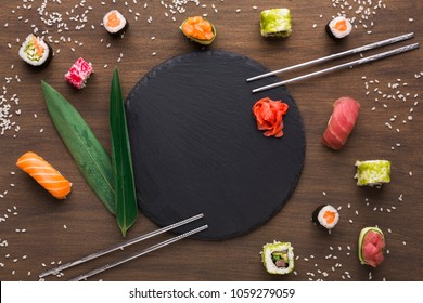 Japanese traditional food. Assortment of sushi served around empty black round slate plate with ginger on wooden background with spilled rice, chopsticks and bamboo leaf, top view, copy space
