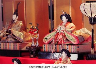 Japanese traditional ornamental hina dolls depicting the Emperor, Empress, and attendants,  all displayed on a red carpet during Hinamatsuri, also known as girls day.