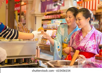 Japanese traditional pancake being served on food stall on open kitchen in Asakusa, japan. Asian girls hand of dessert and wearing beauty kimono during festival event during travel.