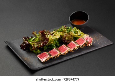 Japanese traditional salad with tuna and sesame on a plate of slate and on a black background. Authentic Japanese food.