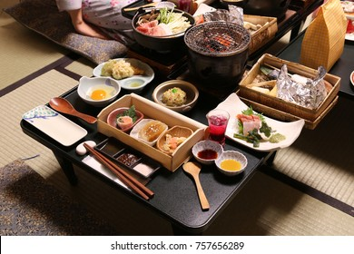 Japanese traditional style set menu consisted of hot pot, grill pot, raw fish pickle, solf drink and other side disk served in traditional way for the traveler in Japanese hot spring resort.