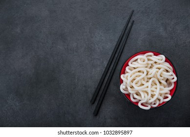 Japanese udon noodles in red bowl on stone table
