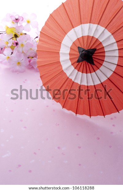 japanese umbrella and cherry blossom on pink background