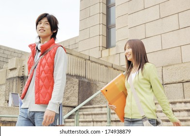 Japanese University student couple going down stairs of university