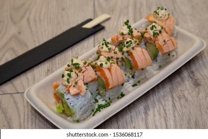 Japanese uramaki sushi. Bebi roll Rice rolls stuffed with tempura shrimp, avocado, chopped lettuce, crispy onion, flambéed salmon topin, anticuchera sauce and chives.