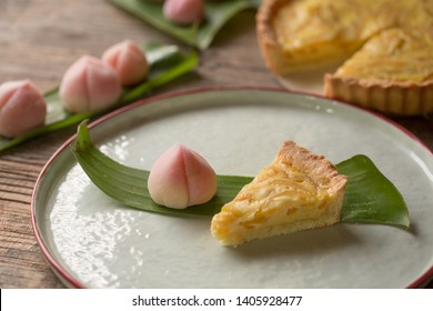 Japanese wagashi shaped in peach, peach shaped wagashi and a slice of tart served on a plate