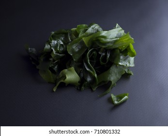 Japanese wakame seaweed soaked in water, isolated on black background