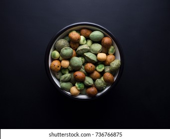 Japanese wasabi crackers in small rustic bowl isolated on black background