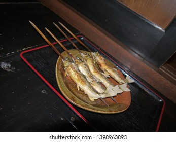 Japanese washoku cuisine salt-Grilled ayu trout sweetfish skewers on lacquered tray