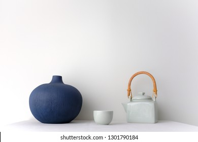 Japanese white ceramic teapot with wooden handle and tea cup and a blue oriental ceramic vase on white table top on white background in natural light with copy space. Minimal Asian interior styling.