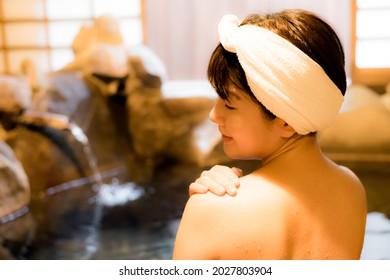 岩でできた温泉に入る日本女性