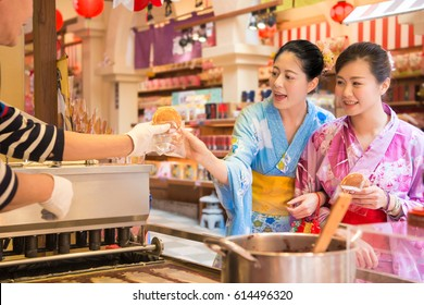 Japanese woman buying pancake, a traditional snack food sold in outdoor market  from japan. Asian girlfriends dress kimono and taste stall food during shopping happy time.