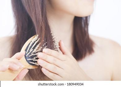 髪に毛をブラシで梳く日本の女性