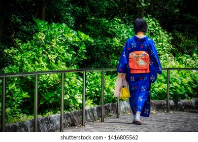 A Japanese woman, dressed in a traditional kimono, walks alone in a park.