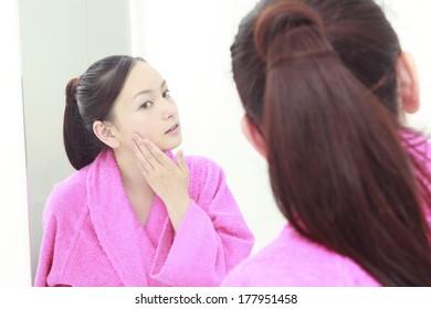 Japanese woman examining her skin