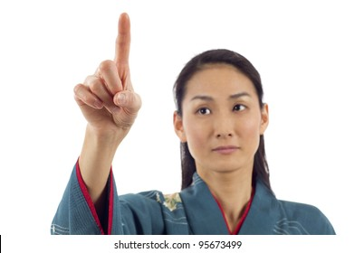 Japanese woman in kimono pointing her finger on imaginery virtual button isolated over white background
