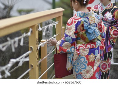 Japanese woman in Kimono reading O-mikuji (fortune prediction) strips of paper at shinto shrines and buddhist temple in Japan. Fold up the paper attach a pine tree or a metal wires for bad fortunes.