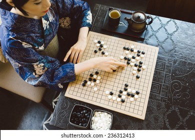 Japanese woman making a move when playing Go boar game