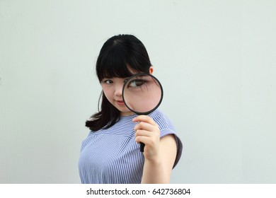 A Japanese woman observing with a magnifying glass