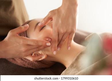 Japanese woman receiving a facial massage at an aesthetic salon