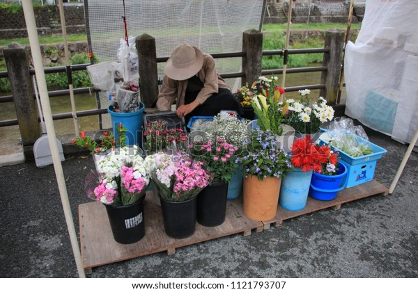 Japanese woman sells flowers in the morning market around the old town, Takayama - Gifu - Japan 27 June 2018