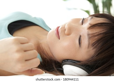 Japanese woman sleeping while listening to music with headphones