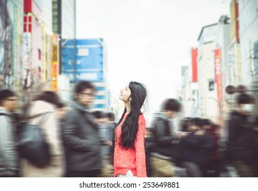 japanese woman standing in the crowd in tokyo city center. she looks amazed at the buildings