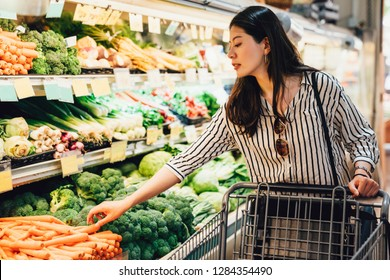 japanese woman in supermarket pushing shopping cart walking by the vegetables and fruits area. pretty asian lady picking up carrots beside broccoli purchase food health care. wife prepare for dinner