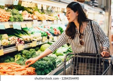 野菜や果物のそばを歩く買い物台を押しているスーパーマーケットの日本女性。ブロッコリーのそばで人参を拾う美しいアジア人の女性は、食べ物のヘルスケアを買う。妻が夕食の準備をする