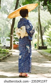 Japanese woman in traditional dress enjoying nature in the park, rear view