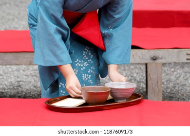Japanese woman in traditional kimono holding tea cups, serving green tea