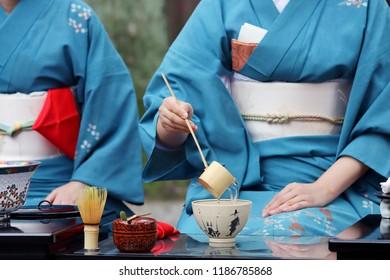 Japanese woman in traditional kimono preparing japanese green tea ceremony at garden