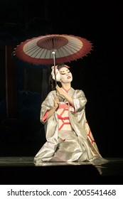 Japanese woman in traditional kimono with umbrella sitting on the knees in darkness, lighten by the moonlignt. Traditional Japanese performance.