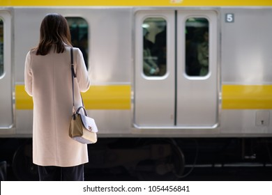 Japanese woman waiting for her commuter train in a busy railway station in Tokyo on a bright spring day.