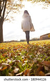 Japanese woman walking through a pile of leaves