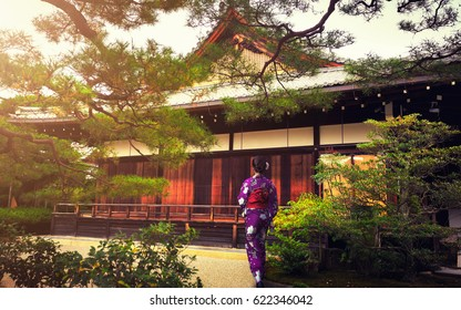 Japanese woman walking with traditional kimono in kinkakuji Temple, Kyoto Japan