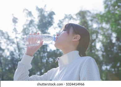 Japanese women with a headphone drink the water in the park