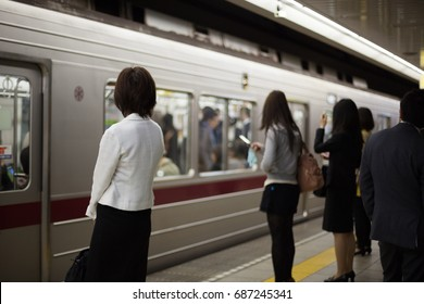 Japanese women waiting for their train on a subway platform in Tokyo.