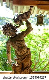 Japanese wood god statue in mitakidera temple garden, Hiroshima