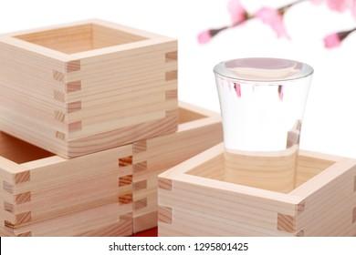 Japanese wooden box masu with sake isolated on white background