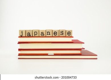 japanese word on wood stamps stack on books, language and academic concept