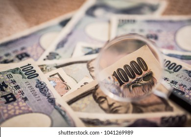 Japanese Yen Banknotes shot stack layers on floor with magnifying glass for selective focus.. japanese currency. financial and economy money concept.