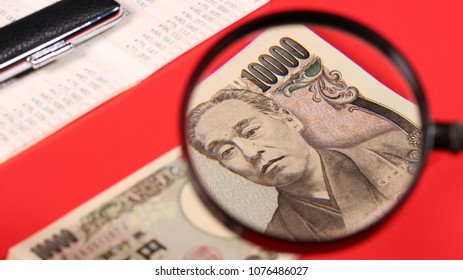 Japanese yen bill and magnifying glass and seal and bankbook