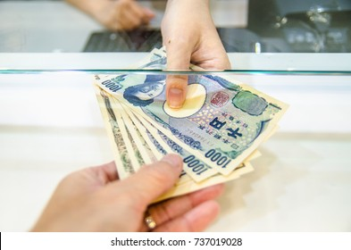 Japanese yen (JPY), Japan money, Women giving money currency of Japan. Exchange money for Japanese yen, business and finance concept.